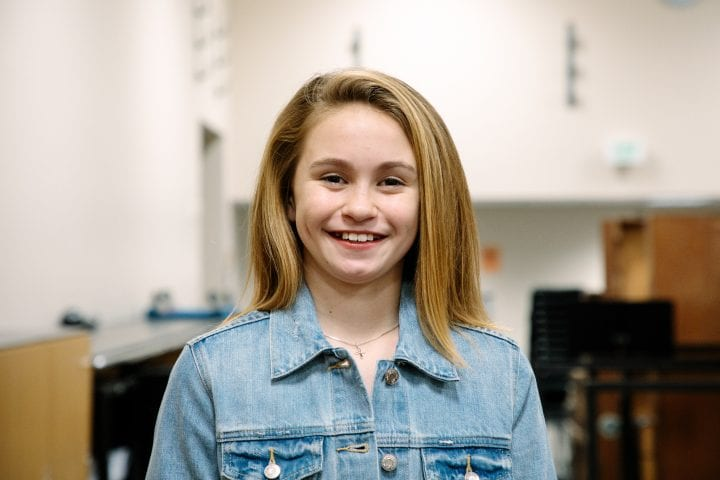 A young girl smiles into a camera backstage, wearing a silver necklace and denim jacket.
