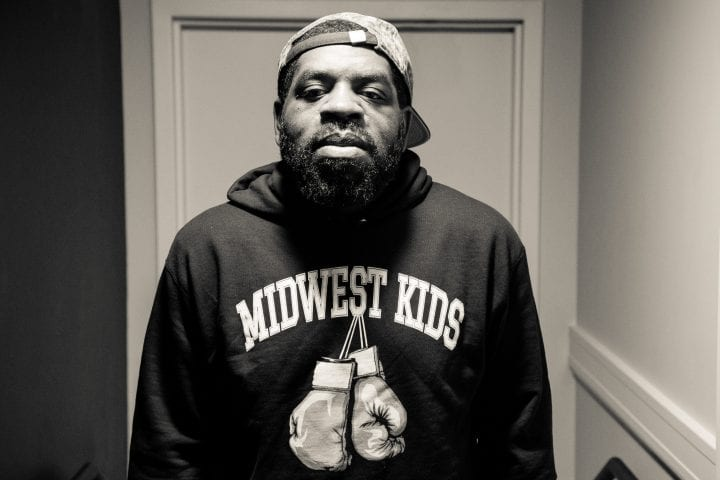 "A black and white shot of a bearded Hanif Abdurraqib, framed in a door frame. He's wearing a graphic sweater with boxing gloves that says ""Midwest Kids."""