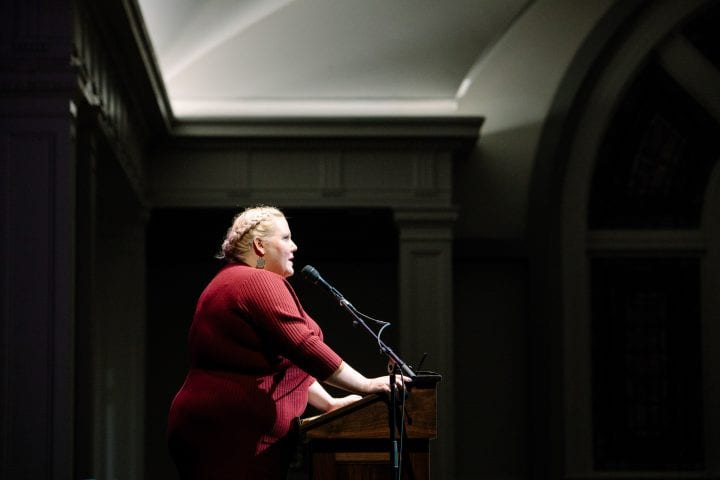 Lindy West, hair braided and wearing a red ribbed sweater, stands at a podium, with both hands powerfully placed upon it. Dramatic light shines down onto her as she speaks into a microphone.